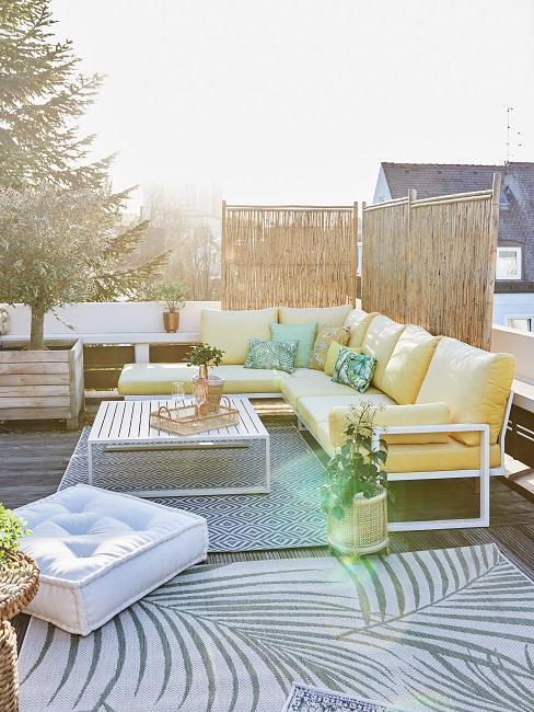 witte tuinset met gele kussens en grijs buitenkleed