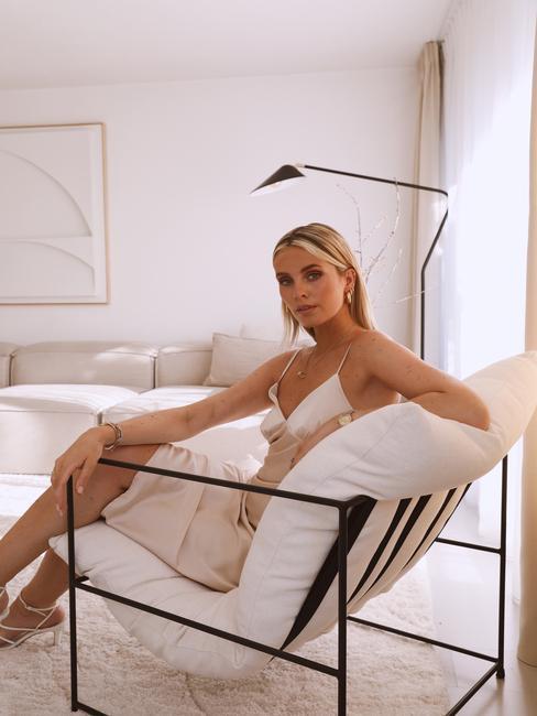 vrouw op een witte stoel met zwarte poten