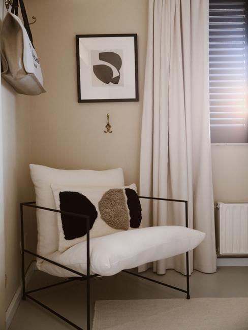 witte stoel met zwarte poten en wit kussen