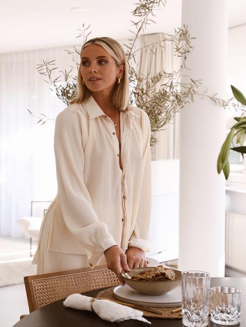 vrouw in een wit overhemd achter een houten stoel