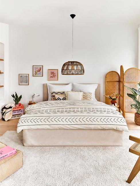 beige bed met een rieten hanglamp