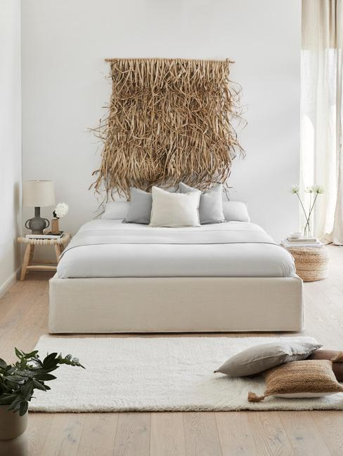 opgemaakt bed met lichtgrijs beddengoed