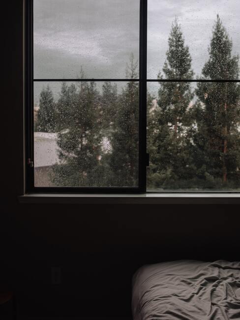raam met donkere kozijnen en een donkere lucht