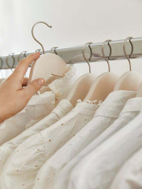 witte bloesjes aan een kledingrek