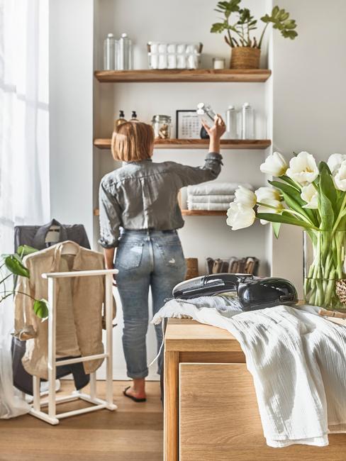 vrouw die een houten schappenkast opruimt