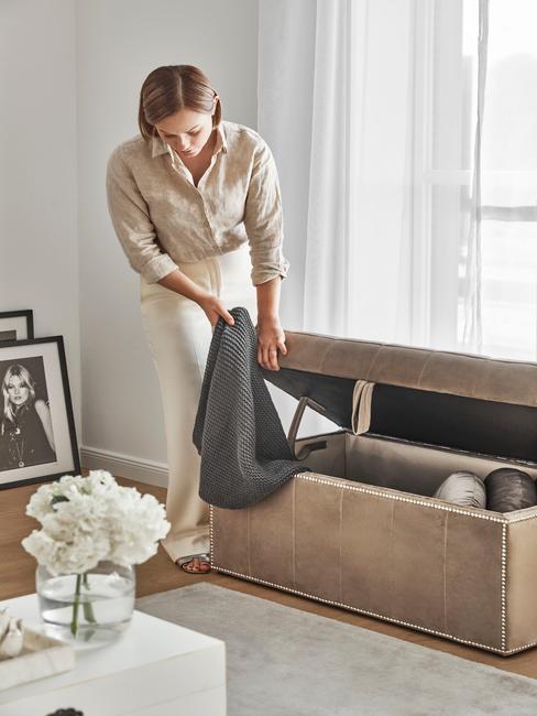 vrouw bergt spullen op in kist