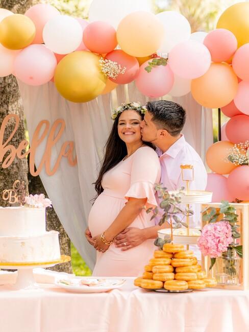 baby shower met vrouw en een man bij een ballonnenboog