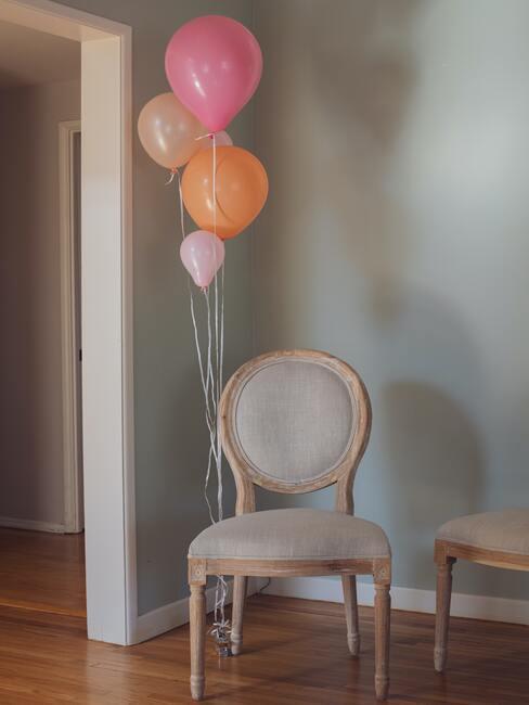 beige stoel met roze ballonnen