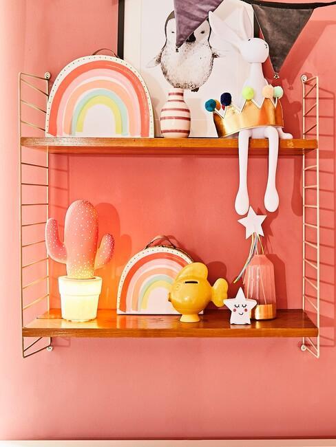 plankjes met speelgoed op oranje muur