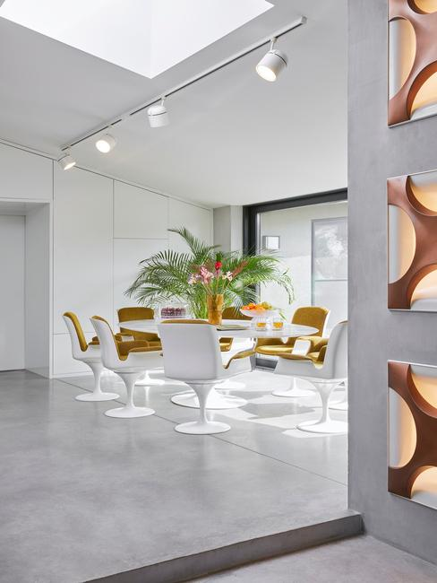 witte schuine kast met een tafel met ronde gele stoelen