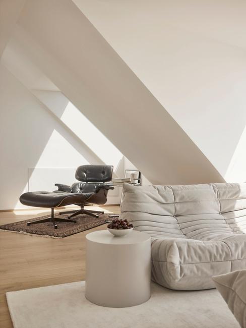 beige stoel met beige poef onder schuin dak