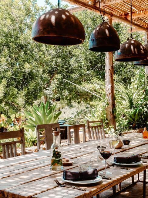 tuintafel met donkere houten hanglampen