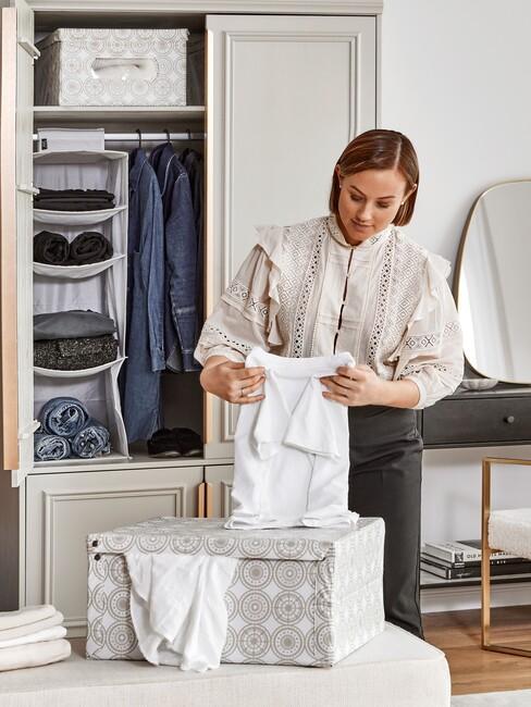 vrouw vouwt wit shirt op