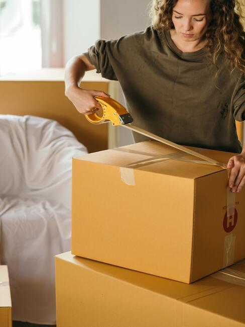 vrouw pakt verhuisdoos in