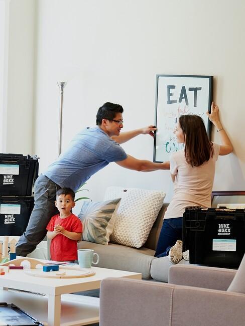 ouders hangen een schilderij op