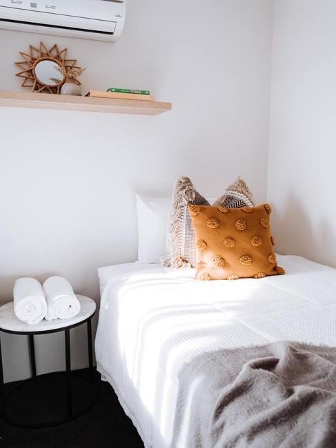 wit bed met oranje kussen