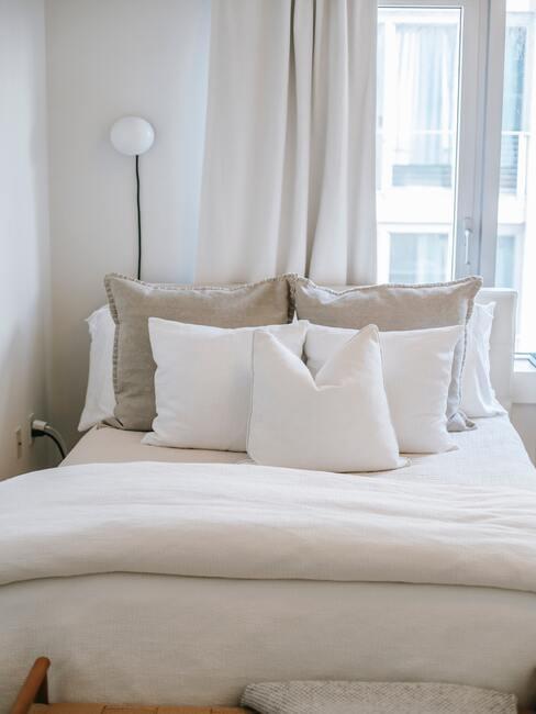 beige bed met witte kussens