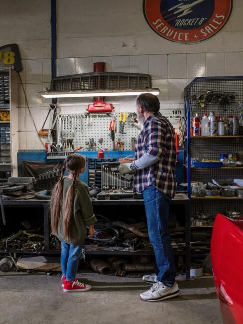 man en kind voor een werkbank in de schuur