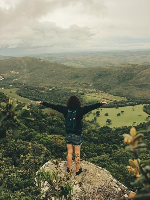 vrouw op een berg neerkijkend op een dal
