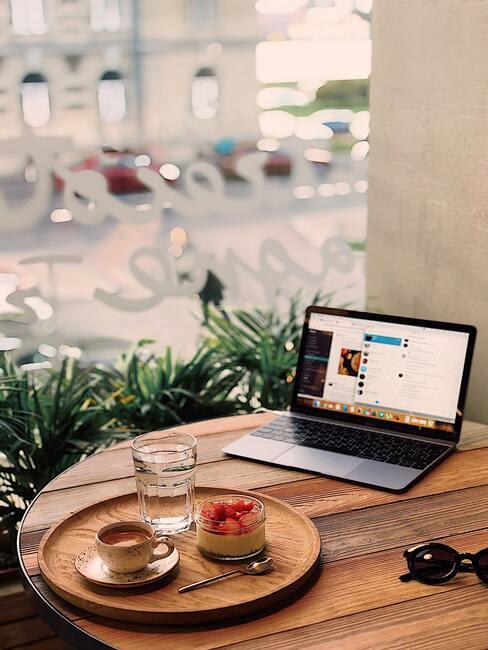 houten tafel met laptop en eten