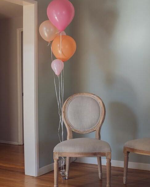 beige stoel met roze en oranje ballonnen