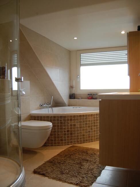 een betegeld bad in een bruine badkamer
