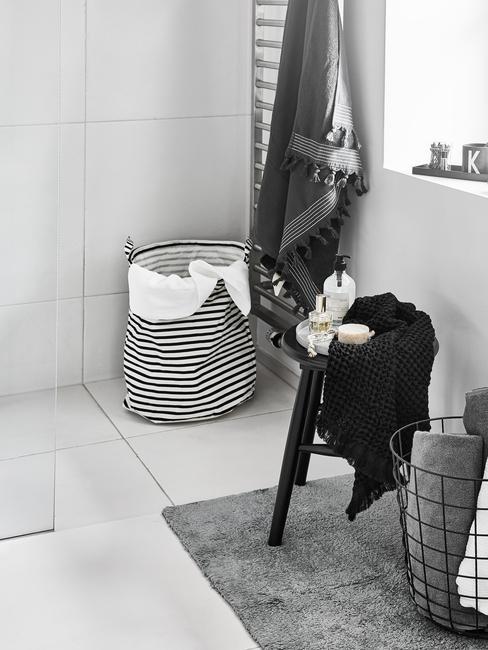 witte tegels met zwarte kruk en mandje