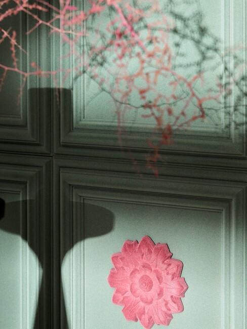 groene muur met textuur en roze bloem