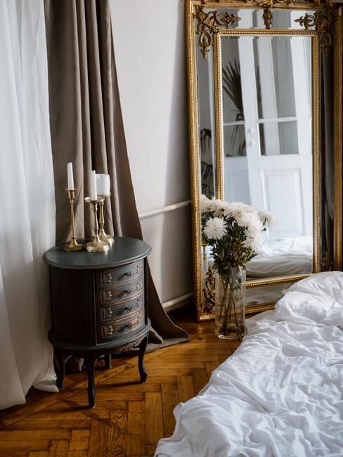 gouden spiegel en donker kastje met glazen vaas