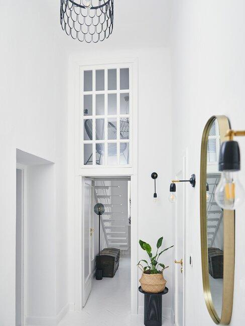witte trap in een wit geverfde hal met gouden spiegel