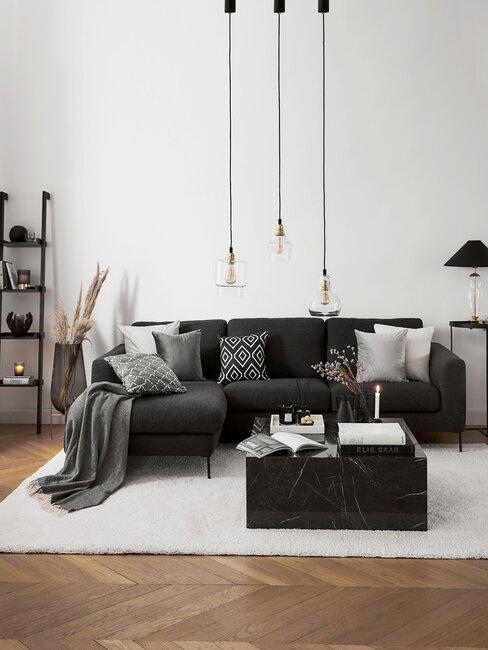 woonkamer met visgraatvloer en zwarte bank