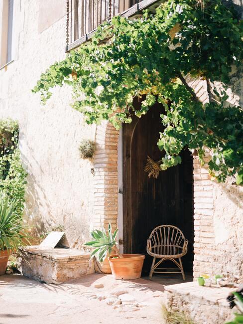 Stenen muur met boog en houten stoel en bankje