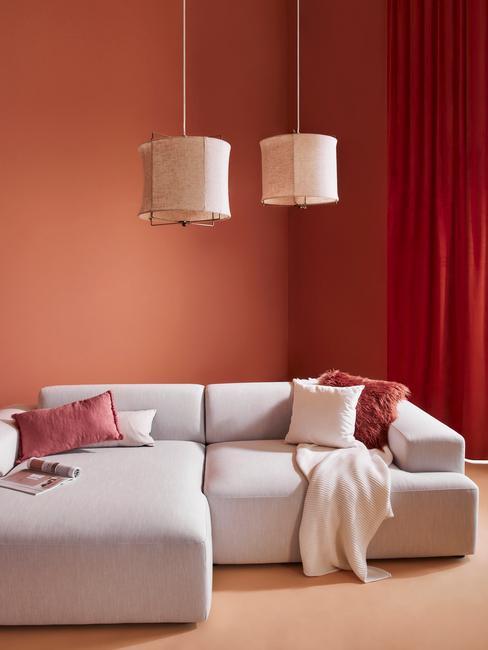 rode muur met grijze bank en roze kussens