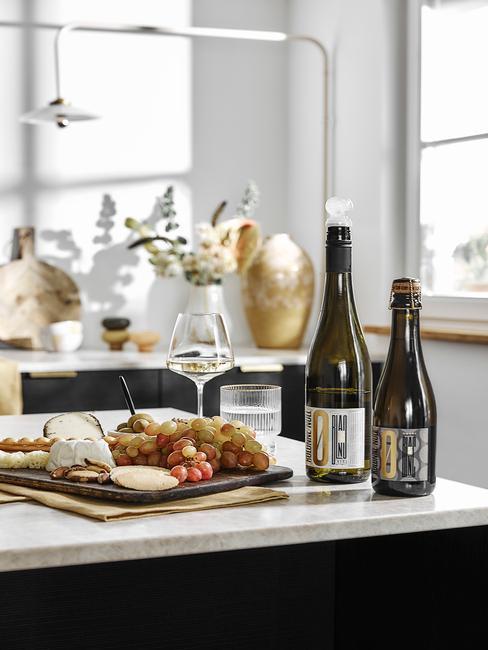 donkere keuken met licht blad met eten en flessen wijn