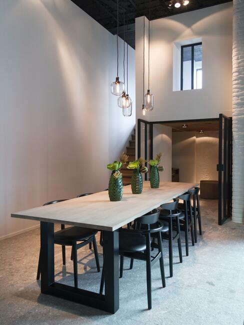 houten tafel met zwarte poten en zwarte eetkamerstoelen