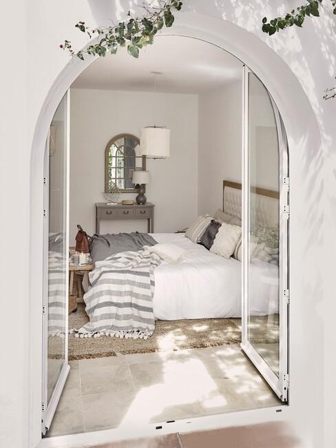 wit huis met boog en wit bed