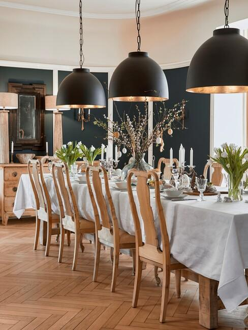 lange tafel met houten tafel en grote zwarte lampen