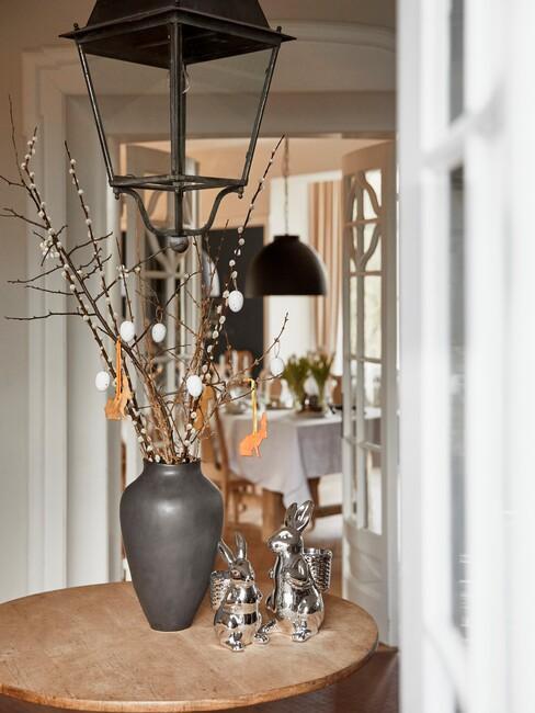 houte ronde tafel met grijze vaas en zwarte lamp