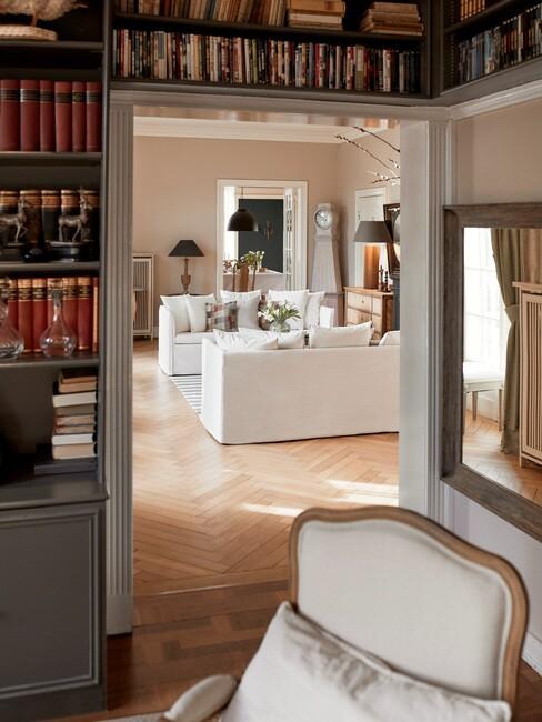 witte banken in woonkamer met een grote grijze boekenkast