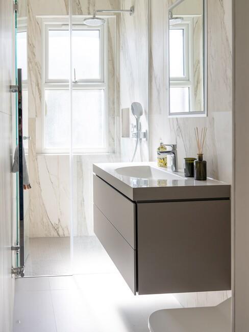 grijs badkamermeubel met witte marmere tegels