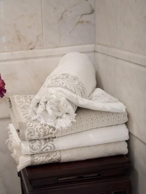 witte handdoeken tegen een marmere muur