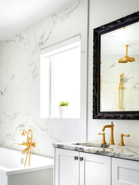 marmeren badkamer met gouden kranen en zwarte spiegel