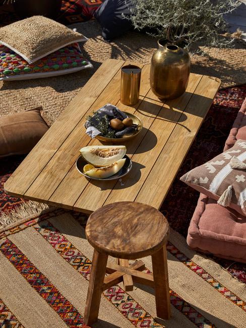 houten tafel met zitkussens en houten kruk