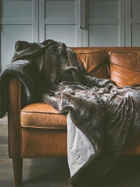Bruin leren bank met grijze aaibare deken