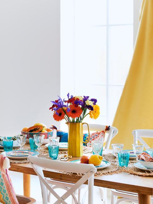 geel met blauw servies op houten tafel met witte stoelen