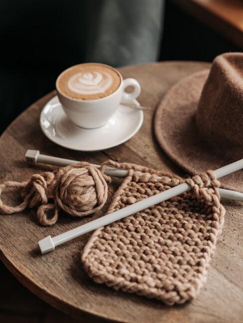houten tafel met brei werk en een koffie