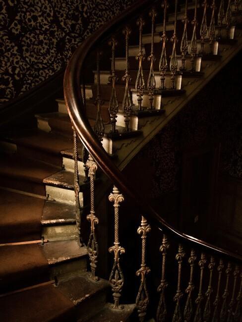 donkere houten trap met houten leuning