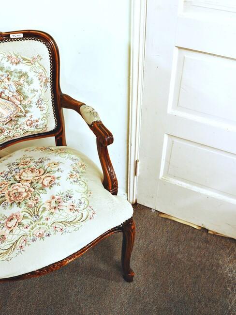witte stoel met bloemen en houten poten