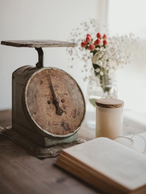 houten klok op een tafel met een boek en witte vaas