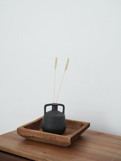 houten tafel met houten schaal en zwarte vaas